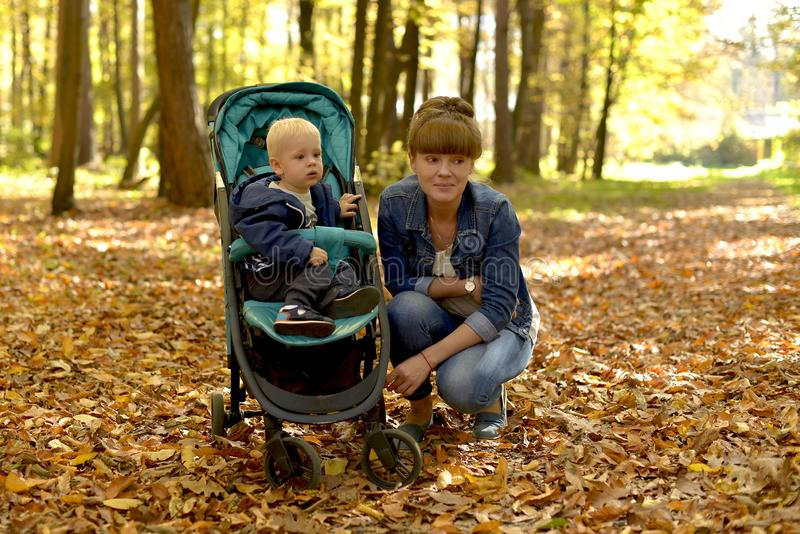 A mother with a baby walking in forest Park a Golden autumn. Mom and baby walk in the forest Park in the fall royalty free stock photos