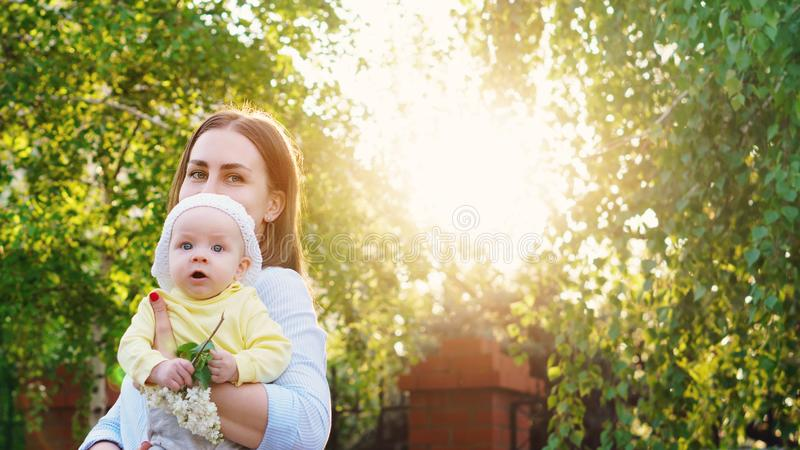 Mom and baby for a walk. Young loving mother walking with her little baby on spring background. Cute child and her mom outdoor. Happiness to be a parent. Time stock photos
