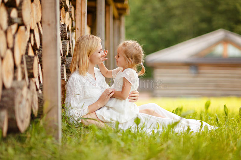 Mom blonde in white dress playing with her daughter on her lap a stock images