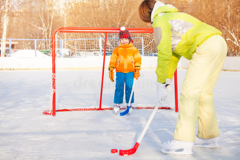 Mom and boy play ice hockey outside on playground. Mom teach little child boy to play ice hockey and hold puck standing near gates on ice stock image