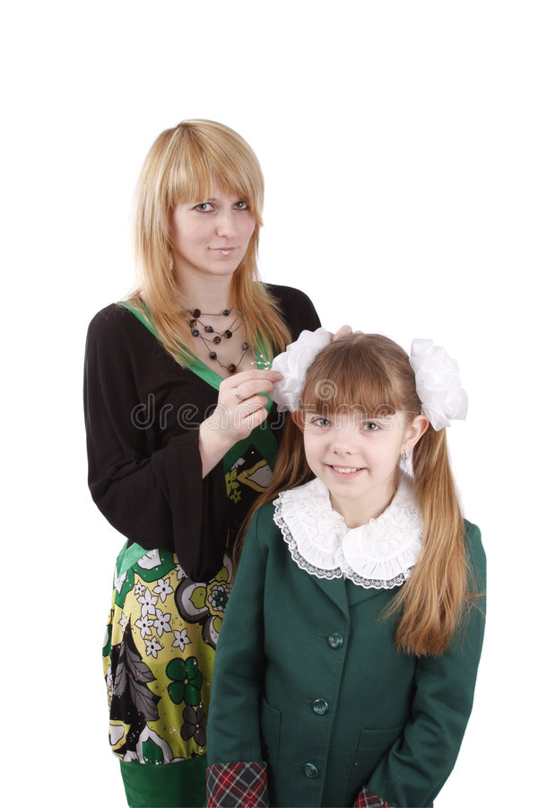Mom is brushing young schoolgirl's hair. stock photography