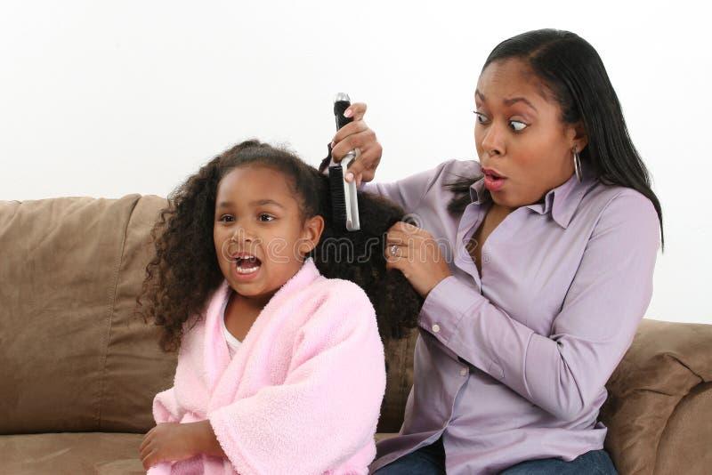 Mom bushing daughter's hair. An African American mom brushing her daughter's hair royalty free stock image