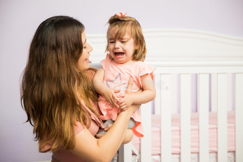 Mom calming down her crying daughter stock photos