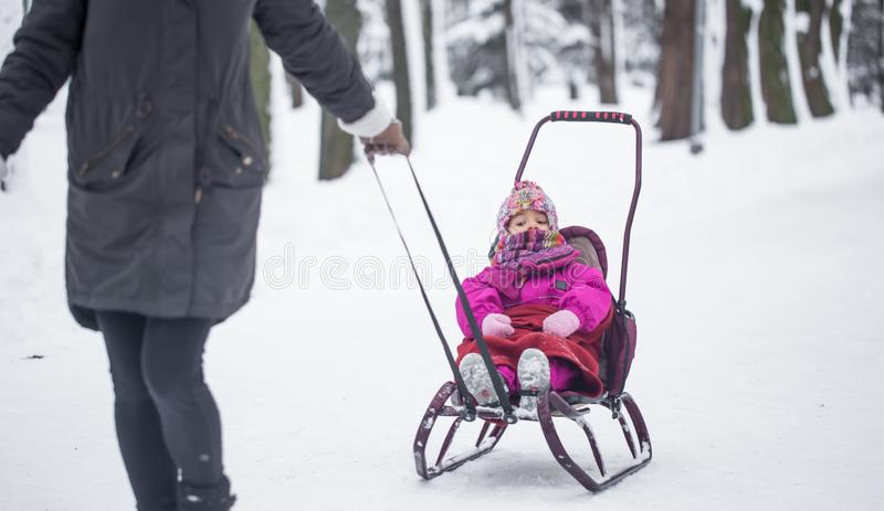 Mom carries her daughter on a sled royalty free stock photography
