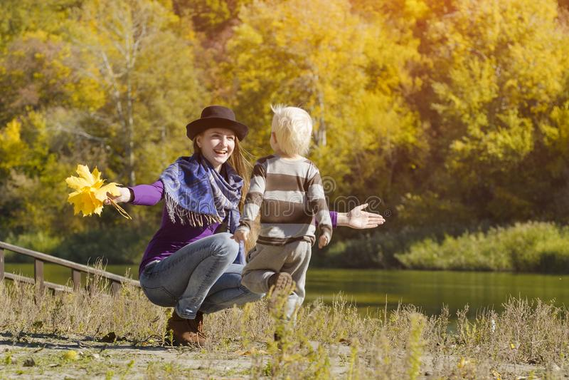Mom catches running son. Autumn, a sunny day. River bank.  stock photos