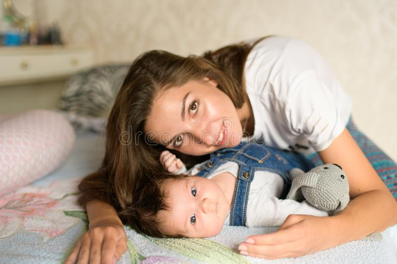 Mom with a child in bed. Happy loving family. Mother and her daughter child girl playing together royalty free stock photos