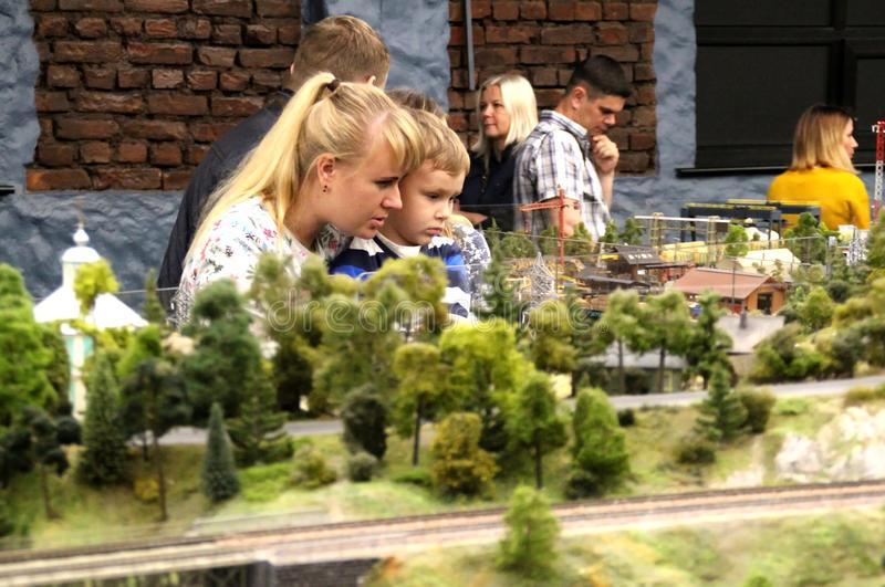Mom with the child are considering the layout. Collective image of cities and regions of the Russian Federation, made in miniature. National show-museum `Grand stock images