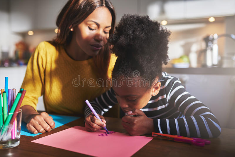 Mom and child drawing. In kitchen, black mother and daughter royalty free stock images