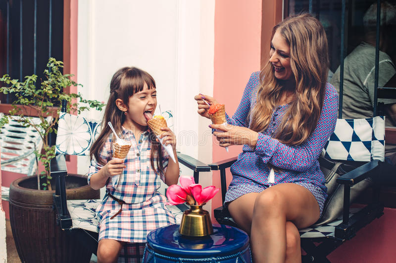 Mom with child eating ice cream in city street stock photos