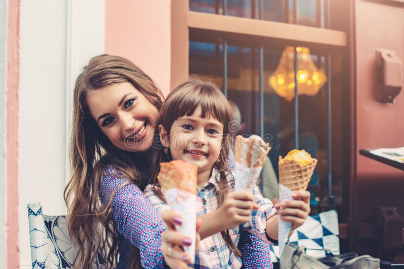 Mom with child eating ice cream in city street stock photography
