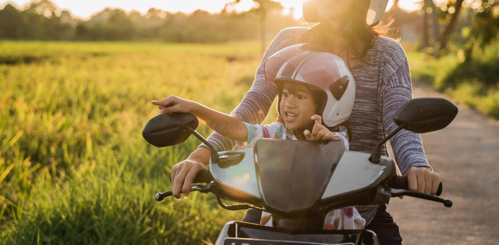 Mom and child enjoy riding motorcycle scooter royalty free stock photo