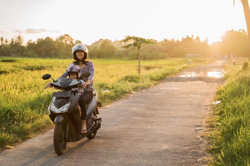 Mom and child enjoy riding motorcycle scooter royalty free stock photos