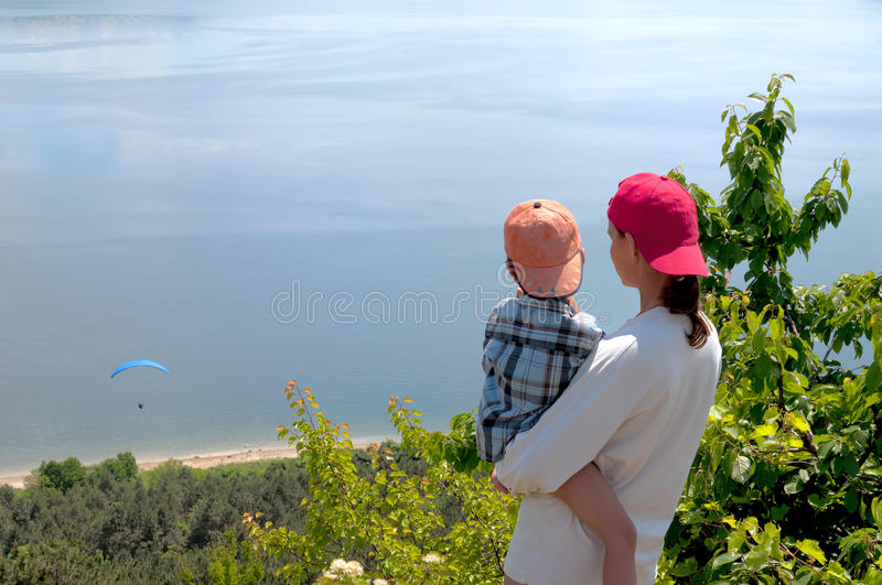 Mom with child in her arms looking flying stock image