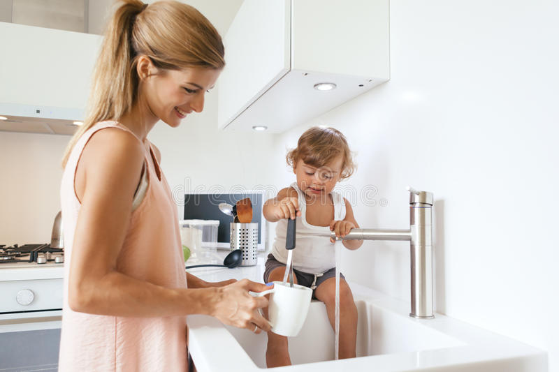 Mom with child in the kitchen stock photography