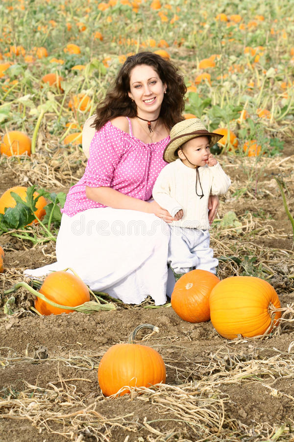Mom And Child Sitting In A Pumpkin Patch Stock Photography