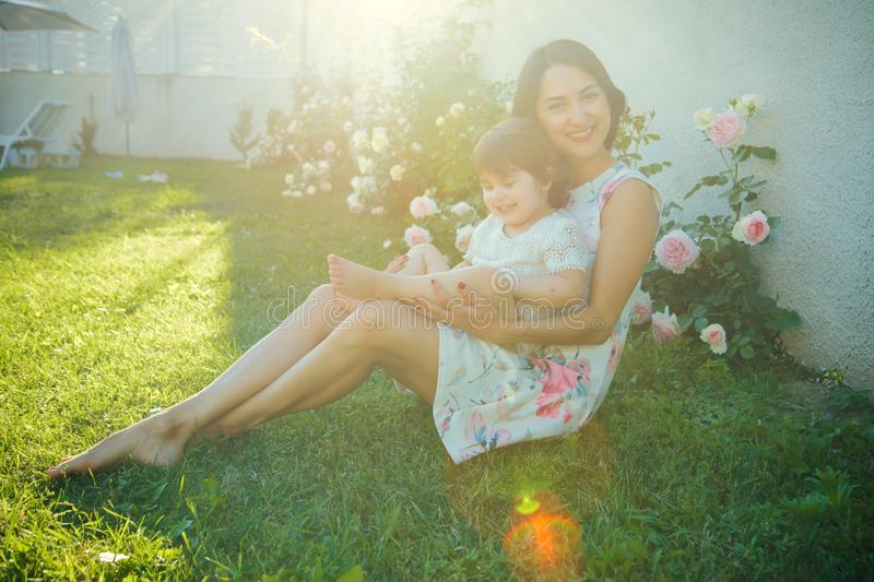 Mom and child smiling at blossoming rose flowers. Woman with baby girl sitting on green grass. Family love and care. Mothers day concept. Nurturing and future stock images