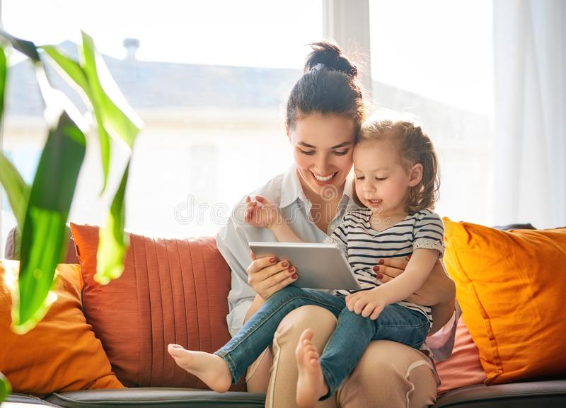 Mom and child with tablet. Happy loving family. Young mother and her daughter girl play in kids room. Funny mom and lovely child are having fun with tablet stock images