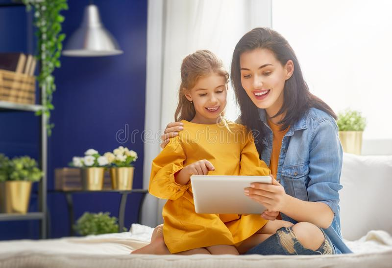 Mom and child with tablet. Happy loving family. Young mother and her daughter girl are playing in bedroom. Funny mom and lovely child are having fun with tablet royalty free stock photography