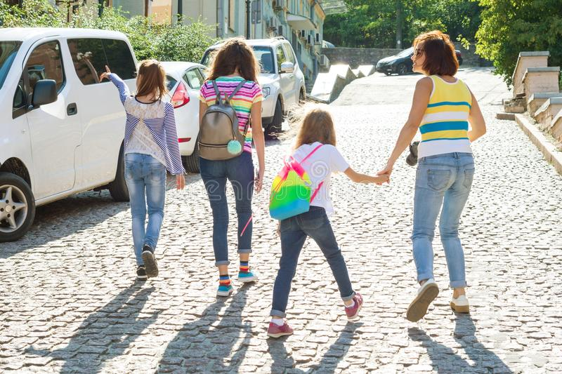 Mom and children holding hands walking around the city. Woman taking pictures at the camera, family tourism. royalty free stock photography