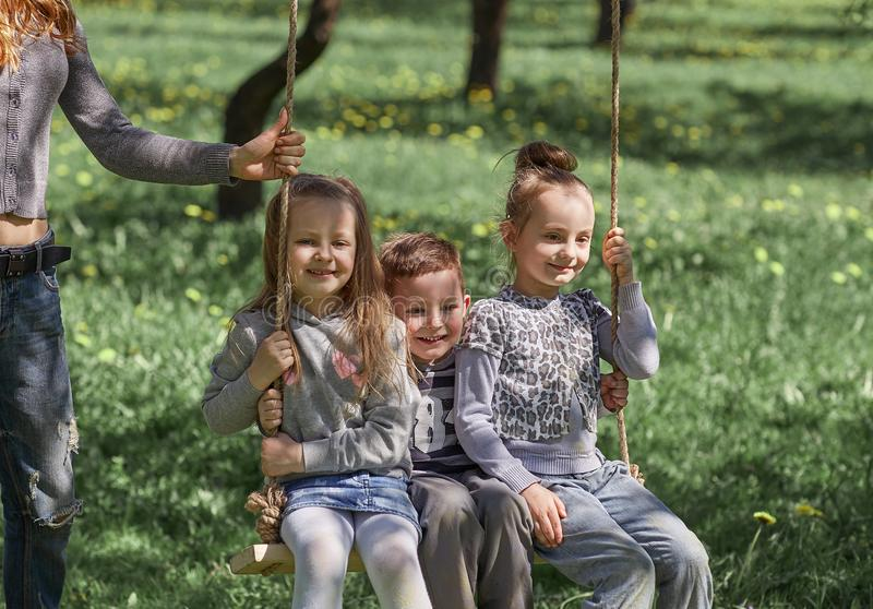 Mom with children playing in the garden on a summer day. royalty free stock photos