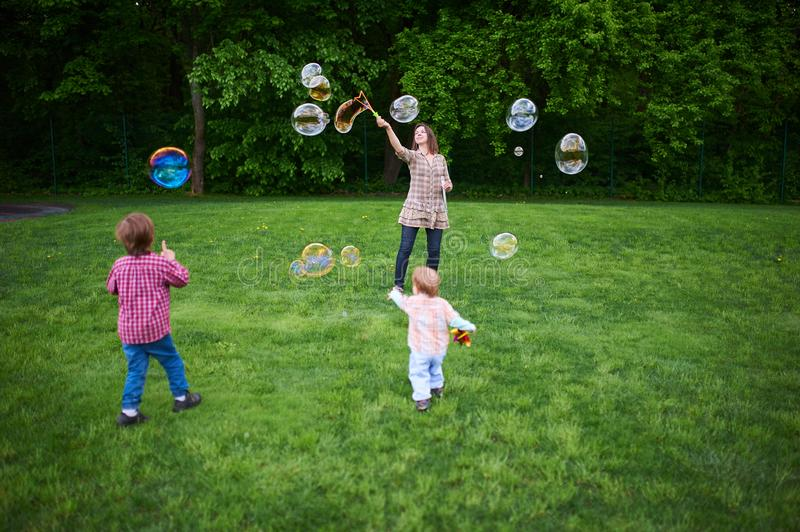 Mom and children playing soap bubbles on the green lawn in the park. Mom and children playing soap bubbles on the green lawn in the park royalty free stock photography