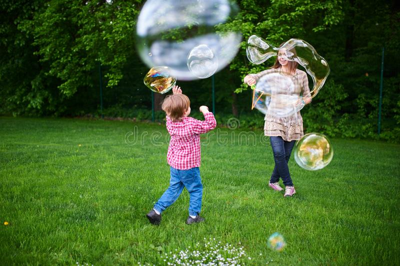 Mom and children playing soap bubbles on the green lawn in the park. Young women blowing soap bubbles on a green lawn royalty free stock photos