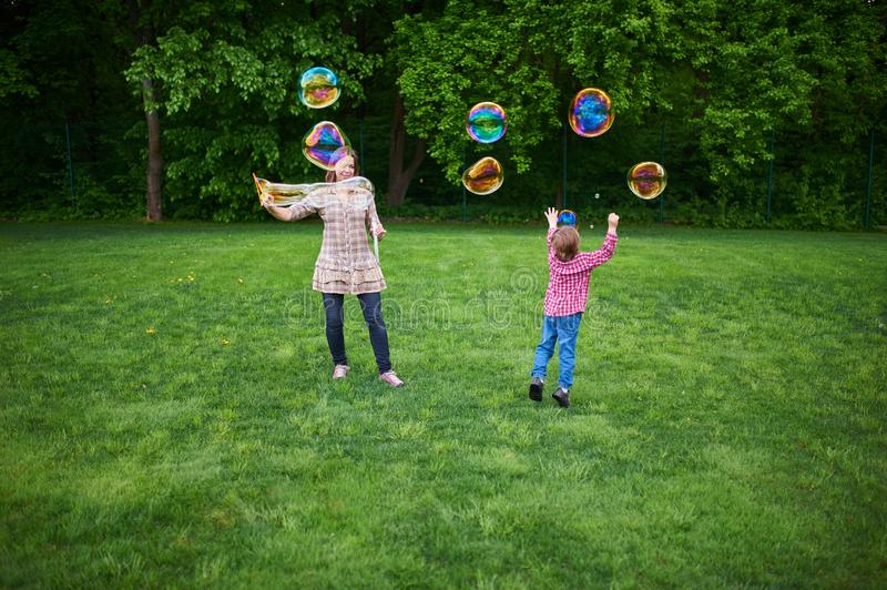 Mom and children playing soap bubbles on the green lawn in the park. Young women blowing soap bubbles on a green lawn royalty free stock image