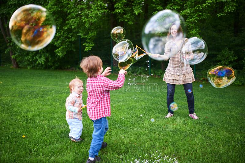 Mom and children playing soap bubbles on the green lawn in the park. Young woman blowing soap bubbles on a green lawn royalty free stock images
