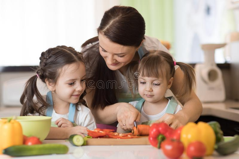 Mom chopping vegetables with kids daughters in a family home kitchen. Mom chopping vegetables with two children daughters in family home kitchen royalty free stock photography