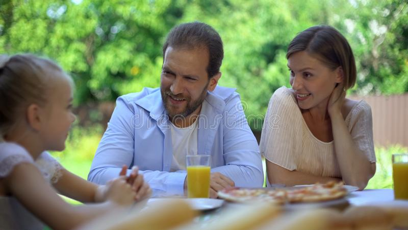 Mom and dad carefully listening to girl telling about achievements, being proud stock photography