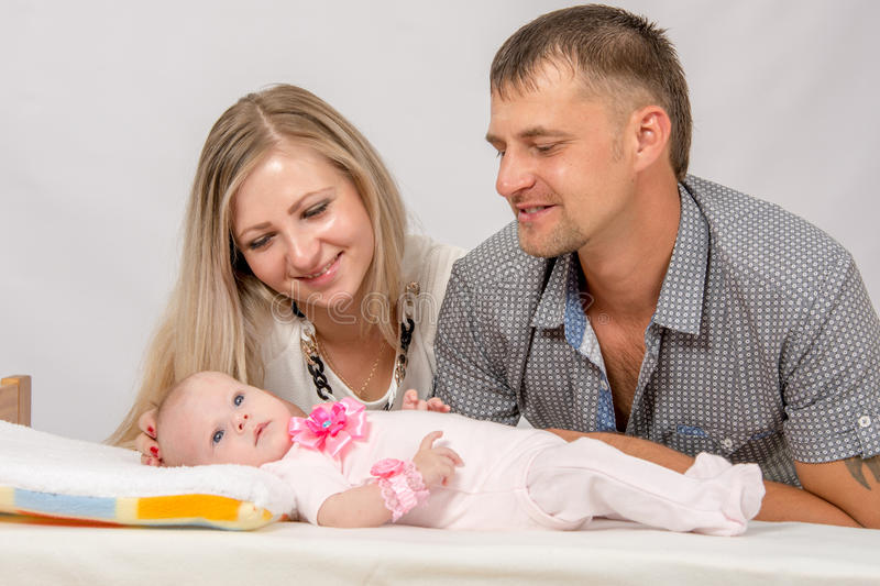 Mom and Dad are considering their two-month baby. Young parents Mom and Dad sit at the crib, the crib on his back lying on the two-month girl stock photo