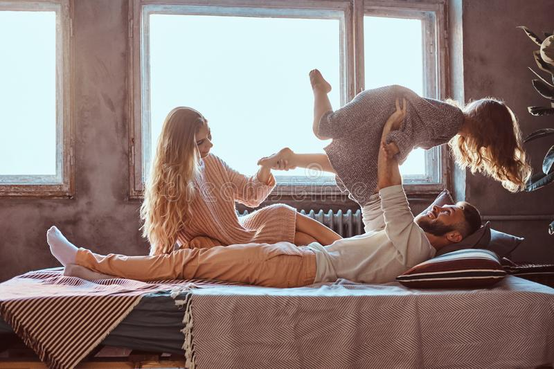 Mom, dad and daughter in bed. Father playing with adorable daughter in bedroom. Family concept. Mom, dad and daughter in bed. Father playing with adorable stock image