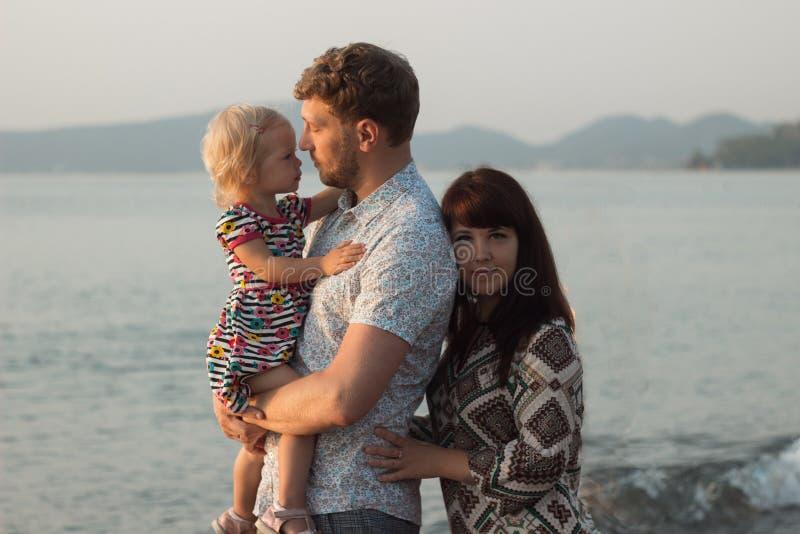 Man Waman and girl on the beach - family stock image
