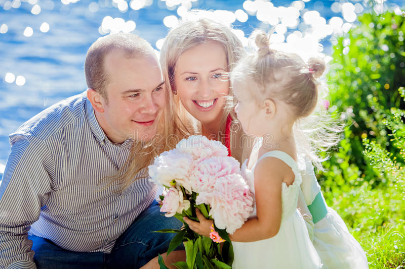Mom, dad and daughter happy on the background of blue water royalty free stock image