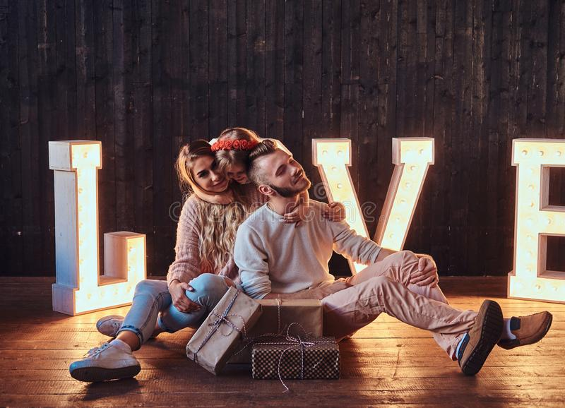 Mom, dad and daughter sits together with gifts in room decorated with voluminous letters with illumination. Love and family concept. Mom, dad and daughter sits royalty free stock photo