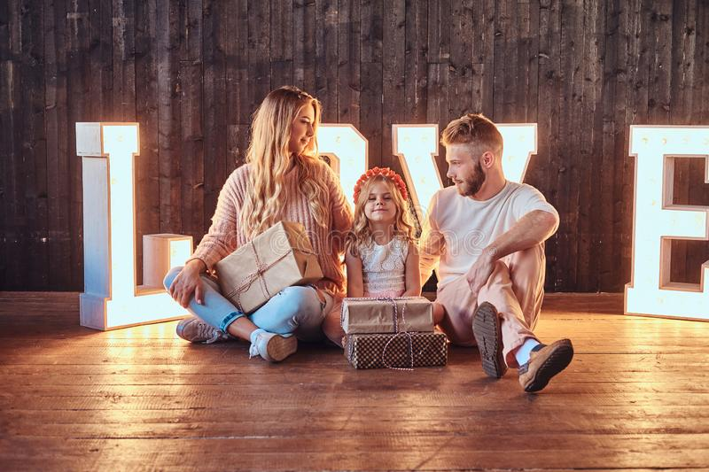 Mom, dad and daughter sits together with gifts in room decorated with voluminous letters with illumination. Love and family concept. Mom, dad and daughter sits stock photo