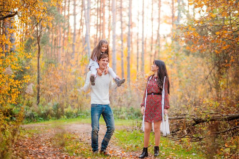 Mom, dad and daughter walk through the autumn forest. Daughter sits on father`s shoulders royalty free stock photos