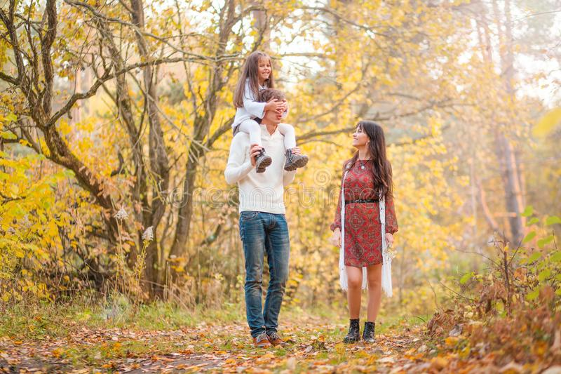 Mom, dad and daughter walk through the autumn forest. Daughter sits on father`s shoulders stock images