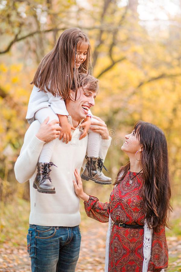 Mom, dad and daughter walk through the autumn forest. Daughter sits on father`s shoulders stock photography