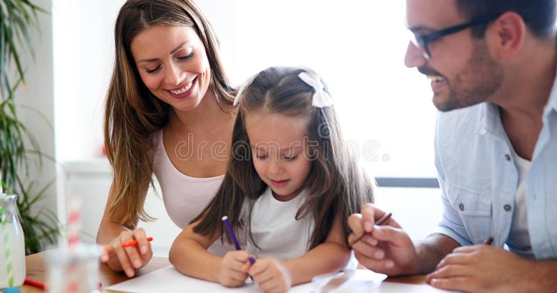 Mom and dad drawing with their daughter stock photo