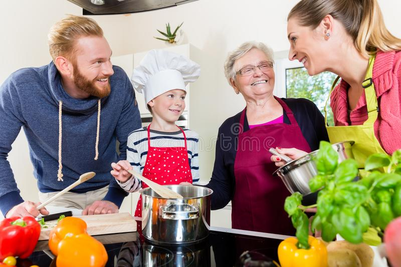 Mom, dad, granny and grandson together in kitchen preparing food stock photo