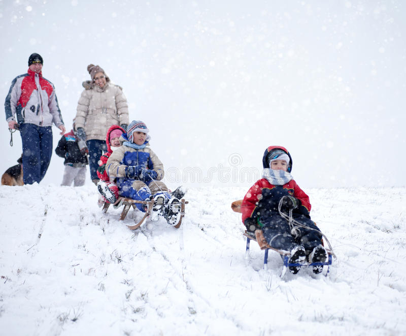 Mom, dad with kids having fun in the snow. Sledding,snow, children on a wooden sleds playing stock photos