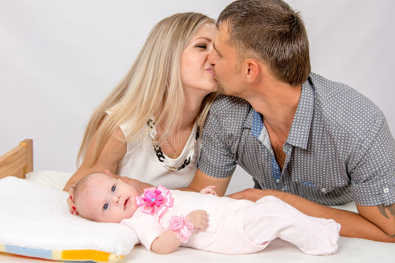 Mom and dad kiss each other while sitting next to a two-month baby. Young parents Mom and Dad sit at the crib, the crib on his back lying on the two-month girl royalty free stock photos