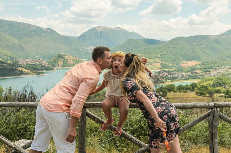 Mom and Dad kiss their daughter on the background of a mountain lake Lago del Turano - happy family royalty free stock photos