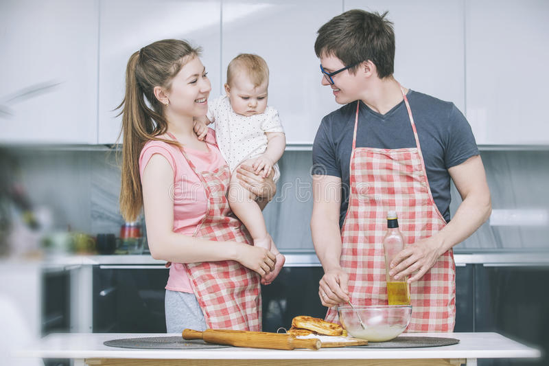 Mom, dad and little baby cooking cakes in the kitchen together a stock images