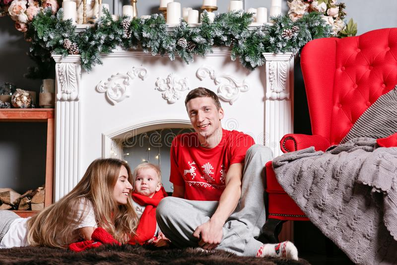 Mom, dad and little baby son . Loving family Merry Christmas and Happy New Year. Cheerful pretty people. Parents and. Loving family Merry Christmas and Happy New royalty free stock photography