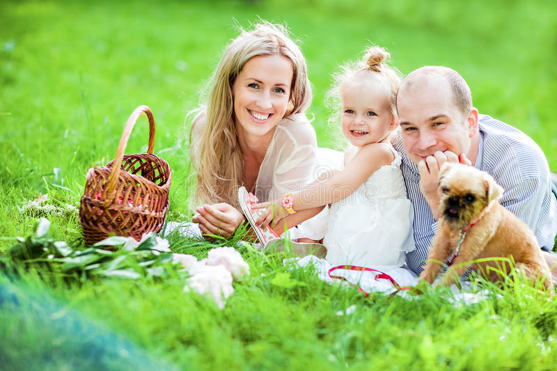 Mom, dad, little girl blonde and dog lie together on the grass a royalty free stock image