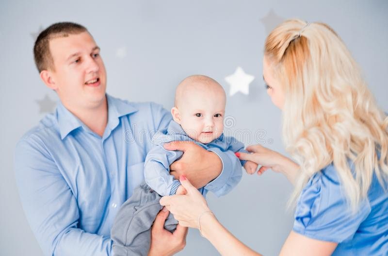 Mom and dad play with the baby throwing it up. Photo of mom and dad play with the baby throwing it up stock image