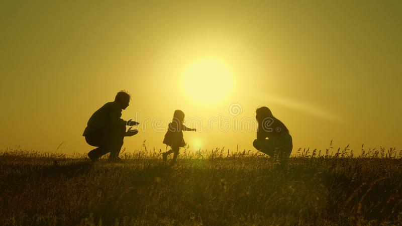 Mom and dad play with their little daughter. happy child goes from father to mother. mother and Dad play with their stock photography