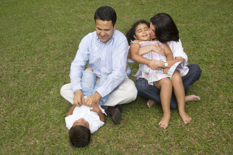 Mom and dad playing with their children stock photography